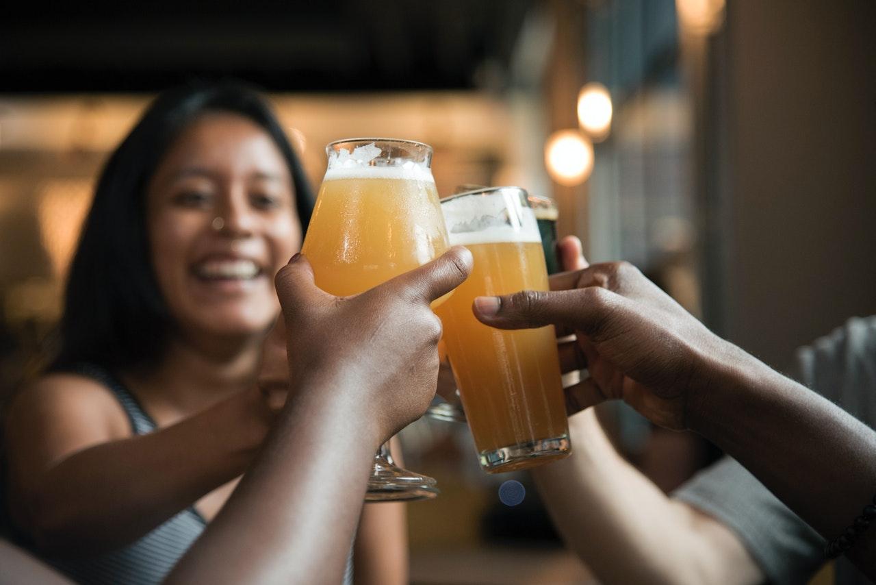 Personer drikker øl sammen på bar